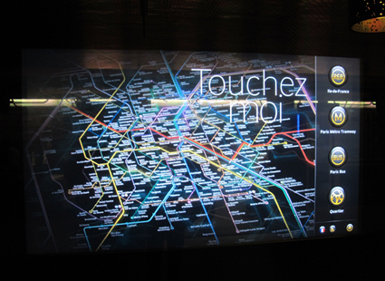 An interactive map at Franklin Roosvelt Paris metro station and an advertising buildboard at the same location. Photos by Carola Moujan.